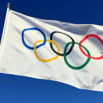 rio-de-janeiro-february-12-2015-an-olympic-flag-flutters-in-slow-motion-wind-against-bright-blue-sky_b4tqupbv__F0007